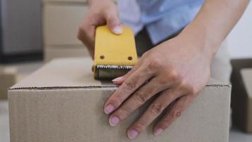 um homem embalando produtos com fita adesiva para entrega video