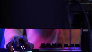joueur utilisant une souris et un clavier éclairés jouant au jeu vidéo en ligne.