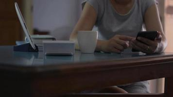 Woman using mobile smart phone and drinking coffee video
