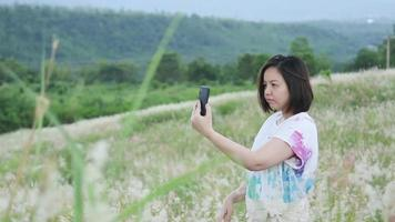 Woman Takes a Selfie with White and Pink Grass Flowers