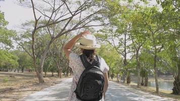 vista traseira traseira da mulher com mochila caminhando em parque público.