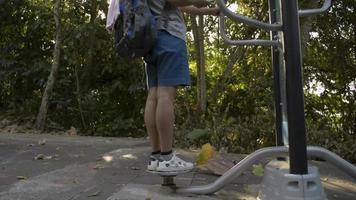 mulher asiática com mochila no equipamento de ginástica enquanto usa o telefone