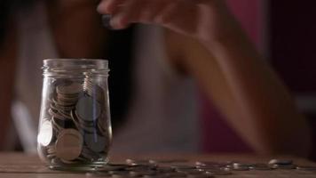 garotinha colocando dinheiro em uma jarra de vidro