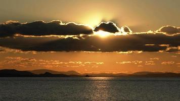 Buque de carga en la línea del horizonte y puesta de sol amarilla