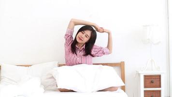 joven, mujer asiática, extensión, y, relajante, en cama