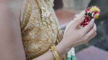 Manos de una mujer vestida tradicionalmente sosteniendo una guirnalda de jazmín