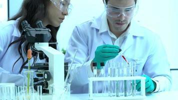cientista experimentando produtos químicos e jogando líquido no tubo. video