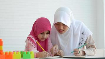 Muslim child with pink hijab learns something with her teacher