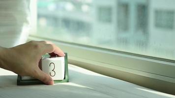 mão trocando um bloco de calendário de madeira branco de 13 para 14