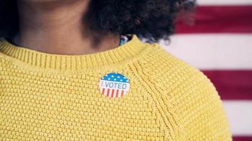"""jovem eleitor colocando adesivo """"Eu votei"""" após a eleição"""