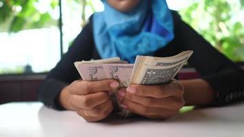 Frau im Hijab, der Banknoten zählt und lächelt