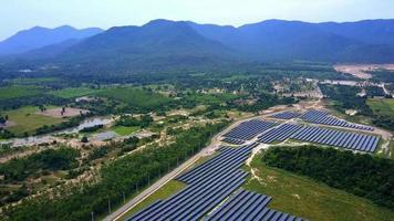 drone voando alto e direto sobre uma grande fazenda solar em um dia ensolarado.