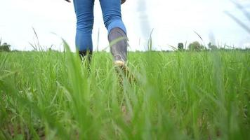 Farmer walking on grass wearing boots