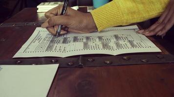 Cerrar joven mujer negra votando por correo boleta ausente