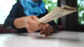mujer musulmana entrega billetes de un dólar a alguien video