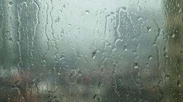 Raindrops trickling down on window glass during heavy rain video