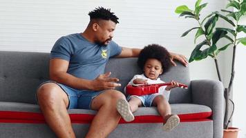 African Father Is Teaching His Toddler Son To Sing And Play Guitar At Home