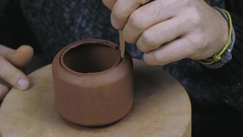 oleiro remove o excesso de argila de um bule