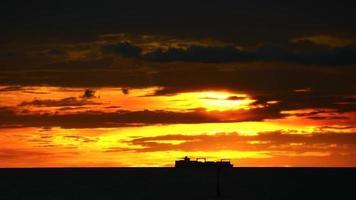 buque de carga moviéndose sobre la puesta de sol
