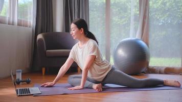 mulher fazendo postura de ioga na sala de estar