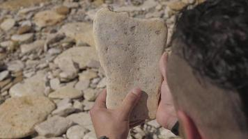 Man holds a sea stone in his hands