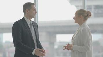 empresário e mulher discutindo sobre um projeto em frente a uma janela