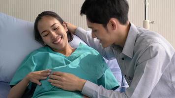 Hombre asiático escuchando el vientre de una mujer embarazada
