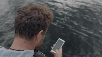 Man sits on a pier and looks at the phone