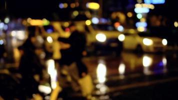 pedestres cruzando a rua em uma noite chuvosa
