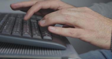 la mano de un hombre escribiendo en el teclado