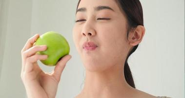 mulher asiática comendo uma maçã verde e sorrindo