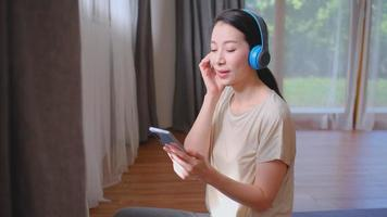 Woman Uses Bluetooth Headphones to Listen to Music from A Mobile Phone