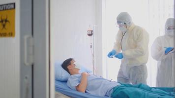 Doctor and Nurse a High Protective Suit Treating an Infected Patient