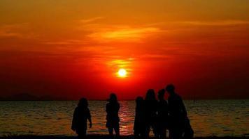silueta, de, amigos, en la playa, durante, ocaso