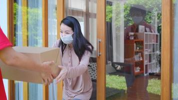 Woman Wearing a Mask Gets a Delivery Package from Carrier Man