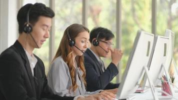 Young Woman Between Two Men Working as a Call Center Operator