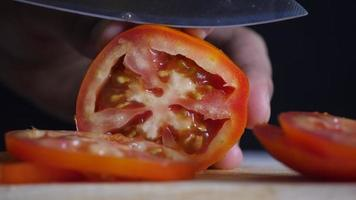 Chef slices ripe tomatoes for cooking