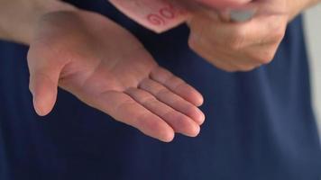 homem segurando notas de baht nas mãos