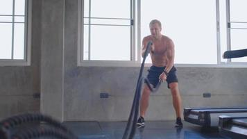 homem se exercitando com corda de batalha na academia