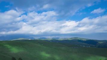 paisagem montanhosa verde com colinas e nuvens