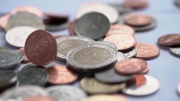 pilha de moedas de baht tailandês, despejando em câmera lenta