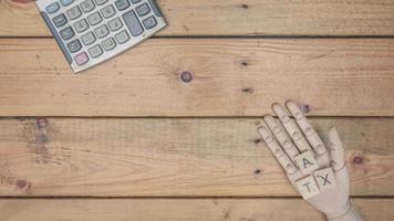 conceito de imposto com mão de madeira e calculadora.