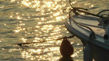 barco de pesca e reflexo do sol na água do mar