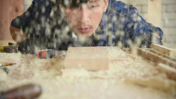 joven carpintero sopla aserrín en el taller