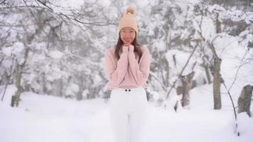 joven mujer asiática en invierno alrededor de la nieve cayendo