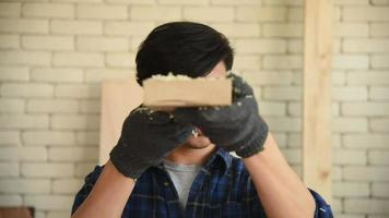 Young Man Blows Sawdust from A Wood Piece in The Workshop