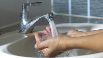 mains attrapant de l'eau sous le robinet
