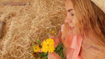 jovem segurando uma flor e cheirando-a