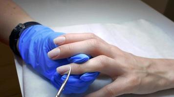 mãos de manicure removendo cutícula de unhas femininas
