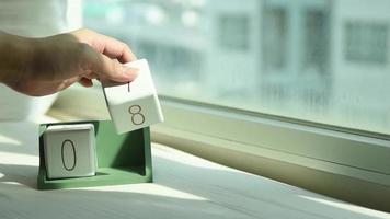 mano que cambia el bloque de calendario de madera blanca de 7 a 8